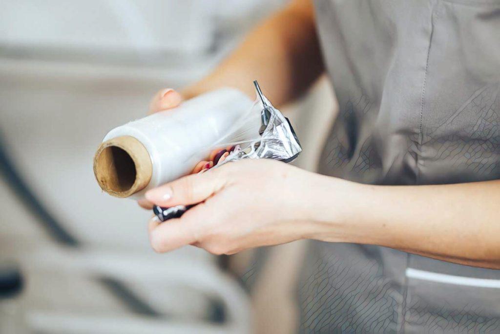 девушка оборачивает тату машинку в пленку